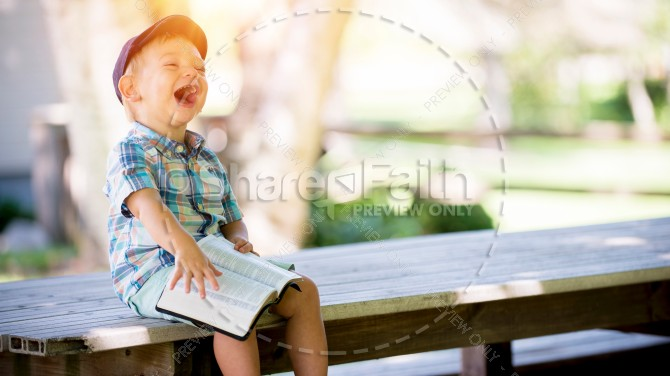 Little Boy Laughing While Reading the Bible Christian Stock Photo